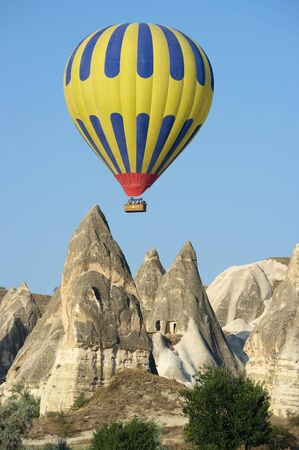 Balloon over Fairy cimneys, typical rock formation in Goreme, Turkey photo