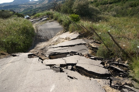 earthquake: the landslide of a rural road on the background an off-road car