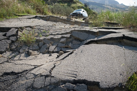 the landslide of a rural road on the background an off-road car photo