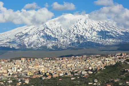Bronte town under the snowy and majestic volcano Etna and a cloudy blue sky photo