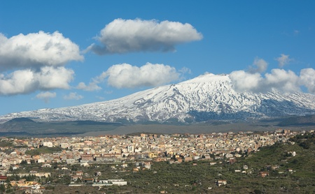 snow capped mountain: Bronte town under the snowy and majestic volcano Etna and a cloudy blue sky