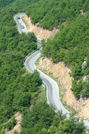 aerial view of cars are going through a mountain road photo