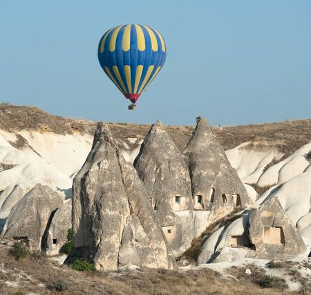 balloon over rock cave houses, typical rock formation in Cappadocia, Turkey photo
