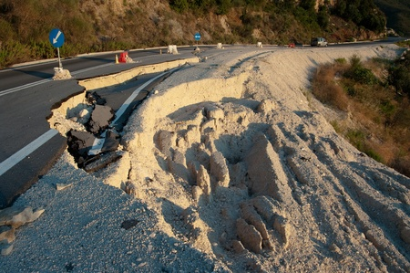 landslip: broken road by an earthquake or landslide (road sign) Stock Photo