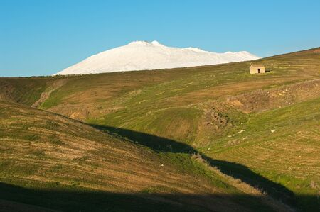green slope with a old shack and white mount Etna snowcapped against the clear sky of evening photo