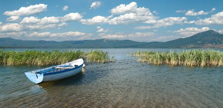 wide view of a row boat and cloudscape on lake Prespa from the macedonian side photo