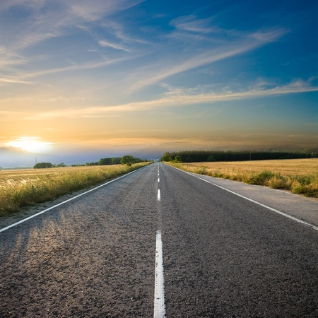 roadway: straight road and colorful sunset Stock Photo