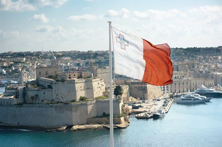 the maltese flag is flying from upper Barrakka gardens in Valletta and on the background the fortifications of Cottonera