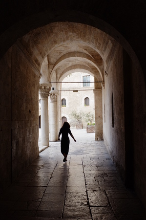 swabian: Bari, Italy - July 08, 2013: a young woman crosses the high arches leading into the courtyard of Norman-Swabian Castle in the old town of Bari. The Castle, a spectacular evidence of medieval architecture, was built by the Normans in the XII century and re