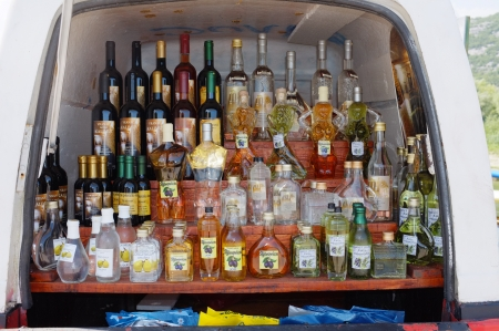 rakia: Virpazar, Montenegro - July 13, 2013  Vranac bottles of wine and fruit distillates well arranged inside a van; Kalimut is a wine made from the grape variety Vranac native of Montenegro and whose manufacturer has been awarded many times, the Sljivovica is  Editorial