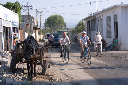 Shkodra, Albania - August 03, 2012  a scene of urban life in a road the suburbs of Shkodra  a scene of urban life in a road the suburbs of Shkodra vehicles are carried by animals, cyclists and cars are mixed in the traffic