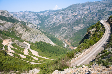a winding dirt road go down into the Valley of the Kelmend between the albanian mountains  photo