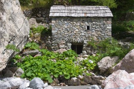 molino de agua: molino de piedra con techo de tejas a lo largo del río Shala en Theth Valley, Albania