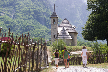 albania: tourists are walking the path leading to the church of the Catholic rite in the National Park Theth, Albania