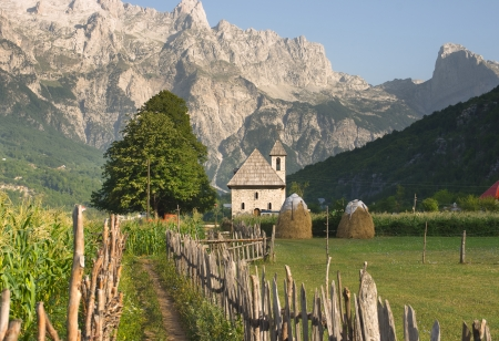 cursed: a path with wooden fence leads the catholic church in the Theth Valley, on background the mountains of Albanian Alps Stock Photo