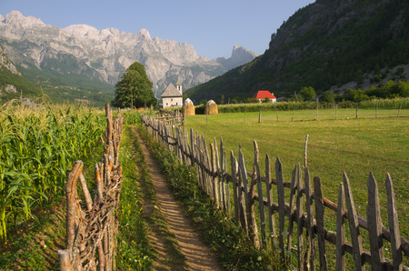 albanian: a path with wooden fence leads the catholic church in the Theth Valley, on background the mountains of Albanian Alps Stock Photo