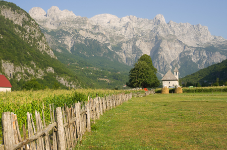 albanian: wooden fence leads the catholic church in the Theth Valley, on background the mountains of Albanian Alps Stock Photo