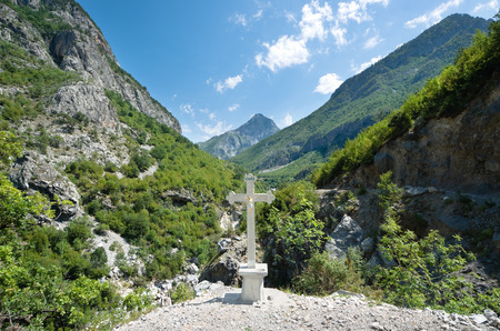 cursed: crucifix on the background the Kelmend mountains; the cross bears witness to the Catholic faith predominant in the mountainous regions in the north of Albania
