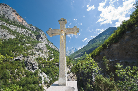 predominant: crucifix on the background the Kelmend mountains; the cross bears witness to the Catholic faith predominant in the mountainous regions in the north of Albania