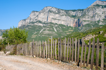 cursed: typical picket fence along rural road to Nikc, on the background the albanian mountains of Kelmend Stock Photo