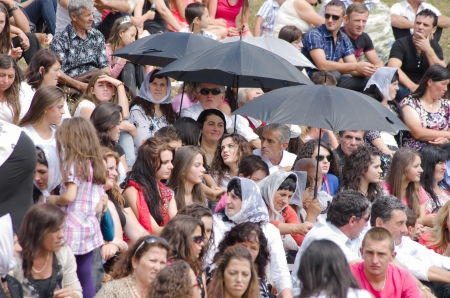 ve: Lepushe, Albania - August 11, 2012  crowd assembled sits at the  Highlanders Festival 2012   albanian  Logu i Bjeshk�ve  some people protect themselves from the sun with the umbrellas  The festival is a popular event that takes place every year since 1998