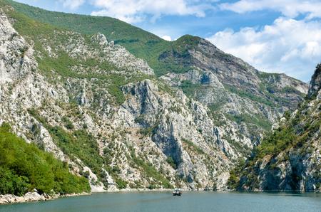 steep cliffs: small boat is sailing between steep cliffs of Koman-Fierza Lake