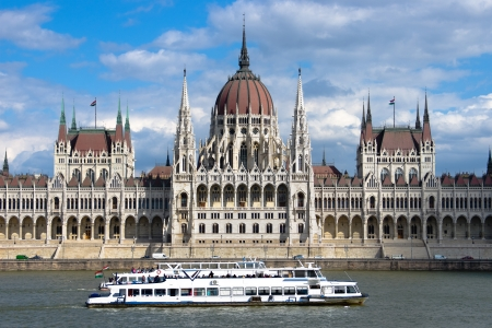 Budapest  a sightseeing boat passes in front of the symmetrical building of the Hungarian Parliament in Pest Stock Photo - 22200001