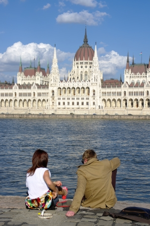 obuda: Budapest, Hungary - April 04, 2012  a young couple are sitting on the riverside of Blue Danube in front of the monumental Hungarian Parliament in new-gothic style of a beautiful spring day in Budapest