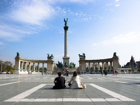 obuda: Budapest, Hungary - April 05, 2012  young couple are sitting in the middle of the Heroes square in front of column topped by statue of the archangel Gabriel Editorial