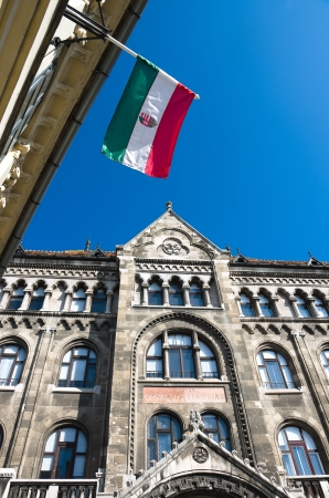 obuda: hungarian flag against blue sky and neo-Gothic facade in Buda Castle district of Budapest