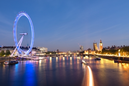millennium bridge: London Eye and Big Ben on the banks of Thames River at twilight