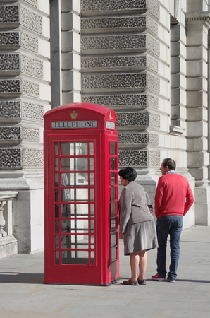 London, England - May 27, 2013  a femal tourist is looking into a red telephone box in London Westminster City  The red telephone boxes were introduced in the 1920s by the post office and were discontinued in the 1990s but had re-appeared in London in rec
