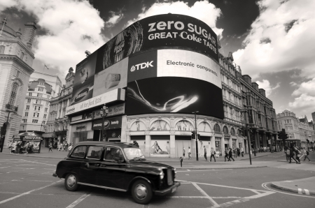 London, England - May 27, 2013  a black cab taxi crosses the iconic video advertising billboards of Piccadilly Circus, a famous public space in London