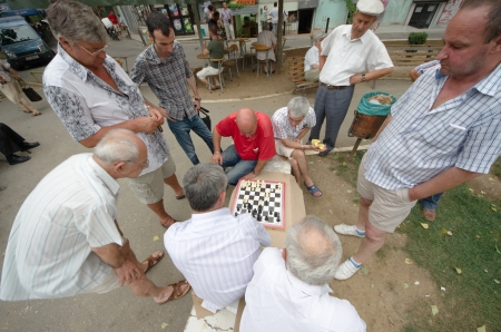 grizzled: Tirana, Albania - July 23, 2012  two middle-aged men playing the match of chess surrounded by other people  The park 1° May  or Cajupi  in Tirana is crowded with more or less young adult men who spend their leisure time playing cards or chess