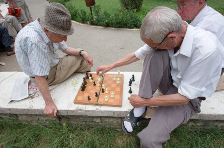Tirana, Albania - July 23, 2012  two middle-aged men playing the match of chess  the player on the right is moving the piece Queen  The park 1� May  or Cajupi  in Tirana is crowded with more or less young adult men who spend their leisure time playing car