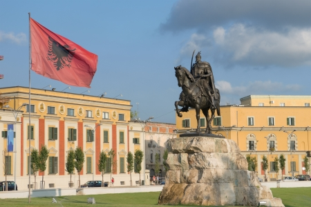 albanian: in the square dedicated to the national hero Skanderbeg dominates its equestrian statue and waving Albanian flag - Tirana Stock Photo