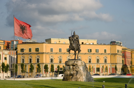 albanian: in the square dedicated to the national hero Skanderbeg dominates its equestrian statue and waving Albanian flag - Tirana Editorial