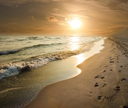 huella pie: puesta de sol de oro en la orilla del mar y las huellas en la arena Foto de archivo