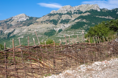 albanian: typical fence made of raw branches along a rural road between Boge and Theth, on the background peak albanian mountains Stock Photo