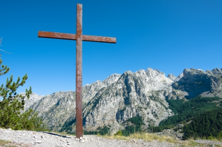 cursed: rusty crucifix on the background the albanian mountains on the road to the Theth Valley; the cross bears witness to the Catholic faith predominant in the mountainous regions in the north of Albania