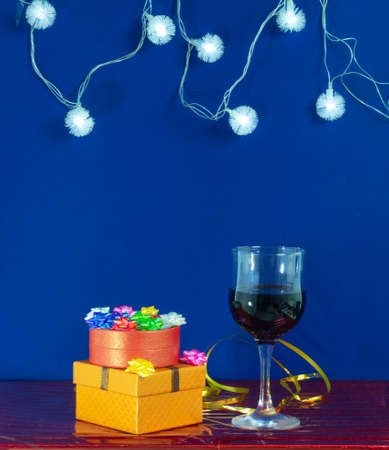 New Years template for the banner. A stack of gifts, a garland and a glass of red wine on a blue background with room for text