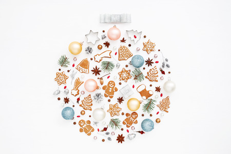 Creative Christmas ball made of gingerbread cookies, balls, pine cones, stars anise, baking molds, acorns, spruce branches on white background. New Year greeting card concept. Top view. Stock Photo