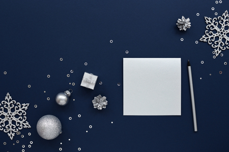 Silver blank Christmas card and a pencil with silvery New Year decorations, gift, snowflakes & sequins on dark blue background. Top view Archivio Fotografico