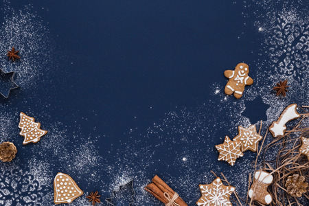 Christmas background with gingerbread and snow on navy colored surface. Holiday mood card. Top view, copy space. Archivio Fotografico
