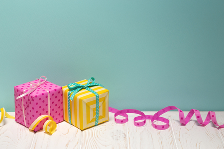 Bright gifts & curling ribbons on white table & blue background. Cheerful Pink & yellow Presents wrapped with paper in polka dots a & stripes. Happy holidays. Minimalism Stockfoto