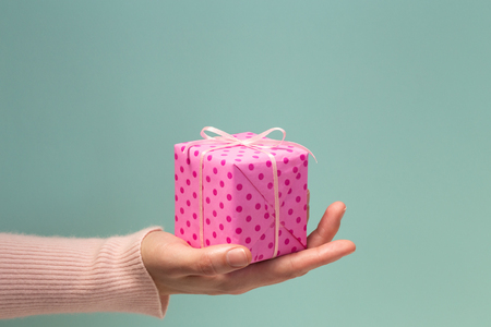 Womans hand giving a gift. Presenting of gift box wrapped with pink paper in polka dots on blue background. Minimal style. Side view, close-up. Happy Holidays, Valentine, Birthday, New Year Stockfoto