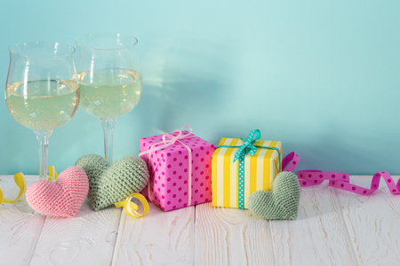 Two glasses of vine, gifts & crocheted hearts on table. Anniversary celebration, Valentines Day, Birthday. Side view, bright colors. Holiday composition on blue background. Stockfoto