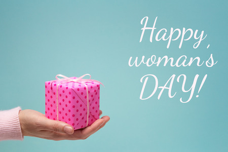 Happy womans day greeting card with womans hand and pink dotted gift box.