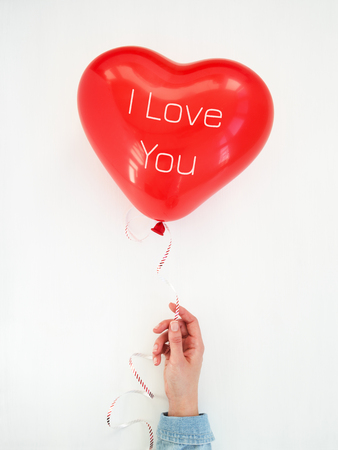 Womans hand holding a Red Heart balloon with inscription I Love You. Valentines Day greeting card.Top view.