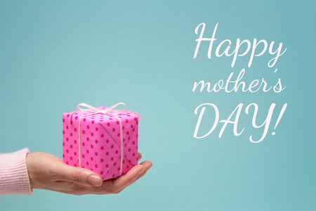 Happy mothers day greeting card with womans hand and pink dotted gift box.